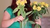 bloemstuk : Female florist puts flowers in a glass vase. To create beautiful bouquet in vase Stockvideo