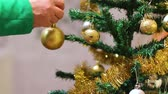presentes : Female hand broadcasts Christmas ball decoration to the Christmas tree on New Years Eve. Holiday home decoration