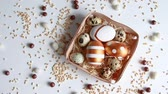 paasei : Decorated Easter eggs in wooden basket with hay on a white table. View from above. Happy easter concept. Scattered wheat and sweets on the table, top view Stockvideo