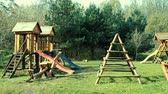 abduction : Childrens playground in summer with swings and slides, made of wooden beams Stock Footage