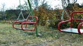 Childrens playground in summer with the red swing, which is empty and swinging Stok Video