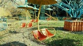 An old abandoned carousel turns in the park in the sunlight