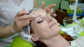 cosmetologist : Beautician applies cream on the face of white woman with hands, area around eyes Stock Footage