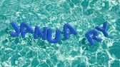beach ball : word JANUARY shaped inflatable swim ring floating in a refreshing blue swimming pool, alpha 3d rendering 4K
