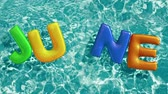 beach ball : word JUNE shaped inflatable swim ring floating in a refreshing blue swimming pool, alpha 3d rendering 4K Stock Footage