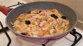 креветка : Shrimps with heads, olives and garlic fried in oil in a pan on a gas stove