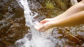 satisfy : Female hands take drinking water from nature waterfall in slow motion video Stock Footage
