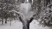 bóbr : man throws up snow in the wood. Slow motion