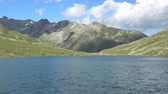 an : Scenic view on peak of mountains and lake in Swiss Alps. Summer landscape, sunshine weather, blue sky and sunny day Stok Video