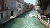 Венеция : Venice, Italy - July 1, 2018: Panoramic view of Venice narrow canal with historical buildings and boats traffic from Bridge Foscari. Landscape of summer sunny day and blue sky Стоковые видеозаписи