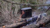 Cooking with cauldron on campfire.