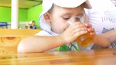 satisfy : boy is drinking a drink from a glass, sitting at a table in a cozy street cafe