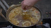 pilau : Meat with rice and vegetables is cooked in a cauldron at the stake. Preparation of pilaf. Stock Footage