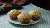 espalhando : Woman take fresh baked muffins out of muffins tin and place them on the plate Stock Footage