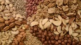 orzech : Nuts mix in a canvas bag in table. Ten kinds of nuts: pecan, brazil, cedar, sunflower, hazelnut, almond, peanut, walnut, pistachio, cashew. The nut mix rotates on the turntable
