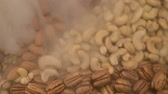 orzech : Nuts mix in a canvas bag. Pecan, brazil, cedar, sunflower, hazelnut, almond, peanut, walnut, pistachio, cashew. Nut mix rotates on the turntable. In the frame there is smoke or steam cold.