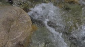 tumultuous : Beautiful water in a mountain river in slow motion video. Shooting speed 180fps, slow motion. Live shooting of the most beautiful nature river mountain water. The camera is not static. Stock Footage