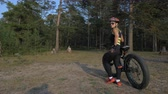 bem aventurado : Fat bike also called fatbike or fat-tire bike in summer riding in the forest. Beautiful girl and her bicycle in the forest. She is posing near her bicycle. Stock Footage