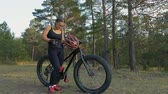 compêndio : Fat bike also called fatbike or fat-tire bike in summer riding in the forest. Beautiful girl and her bicycle in the forest. She is posing and pampering near the bicycle.
