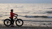 požehnaný : Fat bike also called fatbike or fat-tire bike in summer driving on the beach. Beautiful girl and her bicycle in the beach sand. The girl is out of focus. Focus on the sea.