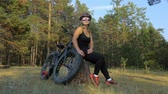 compêndio : Fat bike also called fatbike or fat-tire bike in summer riding in the forest. Beautiful girl and her bicycle in the forest. She sits on the stump and rests from the trip. Stock Footage