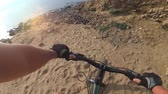 compêndio : Fat bike also called fatbike or fat-tire bike in summer riding. Driving on different surfaces of stones, sand, grass, mud. A view from the first person to the steering wheel, hands and road. Stock Footage