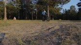 compêndio : Fat bike also called fatbike or fat-tire bike in summer riding in the forest. The guy rides a bicycle on the forest soil. It goes into a controlled skid by the rear wheel. The dust and sand fly into the chamber. Stock Footage