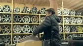 alaşım : The man buys alloy wheels in his shop for his car. He takes a disc out of the box and looks at it. The white wheel is very beautiful and steep. Drawing and form of the disc are thin knitting needles or a star. Stok Video