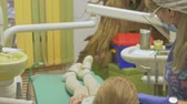clenching : Child with a mother at a dentists reception. The girl lies in the chair, behind her mother. The doctor works with an assistant. Procedure for drilling a tooth. Setting a temporary seal. Using the x-ray machine. Stock Footage