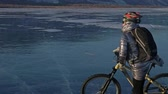 pokrytý : Woman is riding bicycle on the ice. The girl is dressed in a silvery down jacket, cycling backpack and helmet. The cyclist rides and stops to rest. He sits down on the wheel and partially takes off his gear. The traveler is ride a cycle.