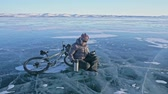 toka : The man is resting sitting on the wheel of a bicycle on ice. He drinks tea from a thermos bottle. The cyclist is dressed in a gray down jacket, backpack and helmet. Ice of frozen Lake Baikal. The tires on the bicycle are covered with special spikes.
