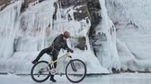 bisiklete binme : Man is walking beside bicycle near the ice grotto. The rock with ice caves and icicles is very beautiful. The cyclist is dressed in gray down jacket, cycling backpack and helmet. The tires on covered with special spikes. The traveler is ride cycle.