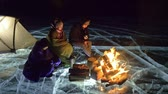 incrível : Three travelers by fire right on ice at night. Campground on ice. Tent stands next to fire. Lake Baikal. Nearby there is car. People are warming around campfire and are dressed in sleeping bags. This is family consisting of father, mother and son.