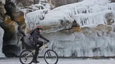 crumble : Man is walking beside bicycle near the ice grotto. The rock with ice caves and icicles is very beautiful. The cyclist is dressed in gray down jacket, cycling backpack and helmet. The tires on covered with special spikes. The traveler is ride cycle.