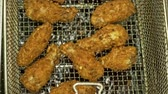 úsek : Deep fryer with boiling oil and chicken. Large, deep fryer container for frying food Buffalo wings. Restaurant deep fryer chicken wing deep fried on hot oil. Chicken wings in breading.