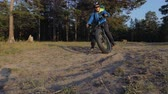 гелий : Fat bike also called fatbike or fat-tire bike in summer riding in the forest. The guy rides a bicycle on the forest soil. It goes into a controlled skid by the rear wheel. The dust and sand fly into the chamber. Стоковые видеозаписи