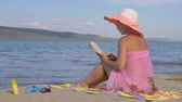 john : Beautiful woman in a silk beach shawl reads an interesting book. She is sitting and reading a book turning the pages. Stock Footage