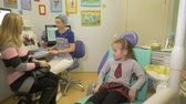 assistente : Child with a mother at a dentists reception. The girl lies in the chair, behind her mother. The doctor works with an assistant. They tell the girl how her teeth will be treated.