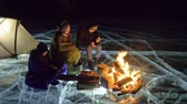éjszakai : Three travelers by fire right on ice at night. Campground on ice. Tent stands next to fire. Lake Baikal. Nearby there is car. People are warming around campfire and are dressed in sleeping bags. This is family consisting of father, mother and son.