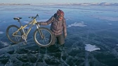 thin ice : Man and his bicycle on ice. He looks at the beautiful ice in the cracks. The cyclist is dressed in a gray down jacket, backpack and helmet. Ice of the frozen Lake Baikal. The tires on the bicycle are covered with special spikes. Stock Footage