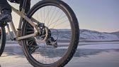 stuntman : Man is riding a bicycle on ice. The cyclist is dressed in a gray down jacket, backpack and helmet. Ice of the frozen Lake Baikal. The tires on the bicycle are covered with special spikes. The traveler is ride a cycle.