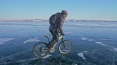 thin ice : Man is riding a bicycle on ice. The cyclist is dressed in a gray down jacket, backpack and helmet. Ice of the frozen Lake Baikal. The tires on the bicycle are covered with special spikes. The traveler is ride a cycle.