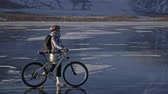 translúcido : Woman is riding bicycle on the ice. The girl is dressed in a silvery down jacket, cycling backpack and helmet. Ice of the frozen Lake Baikal. The tires on the bicycle are covered with special spikes. The traveler is ride a cycle.