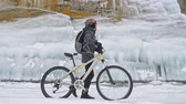 escorregadio : Man is walking beside bicycle near the ice grotto. The rock with ice caves and icicles is very beautiful. The cyclist is dressed in gray down jacket, cycling backpack and helmet. The tires on covered with special spikes. The traveler is ride cycle.