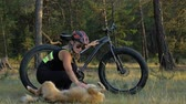 a major : Fat bike also called fatbike or fat-tire bike in summer riding in the forest. Beautiful girl and her bicycle in the forest. She met the dog in the woods and stroked her. The dog is very kind and good.