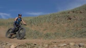 гелий : Fat bike also called fatbike or fat-tire bike in summer driving on the road. The guy rides by the hill on a sand clay path. The bicycle is allowed into the drift. Slow motion shooting 180fps. Стоковые видеозаписи