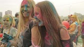 holi : RUSSIA, IRKUTSK - JUNE 27, 2018: Happy young people dancing and celebrating during Music and Holi Festival Of Colors. Crowd of people colored powder and having fun in arena.