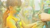 indian eastern : RUSSIA, IRKUTSK - JUNE 27, 2018: Happy young people dancing and celebrating during Music and Holi Festival Of Colors. Crowd of people colored powder and having fun in arena.