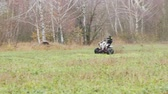 all terrain vehicle atv : the guy with the mask on her face riding her ATV Stock Footage