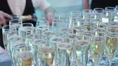 vieira : close-up of champagne glasses standing on the table, the hand of the waiter pours champagne in glasses rise bubbles